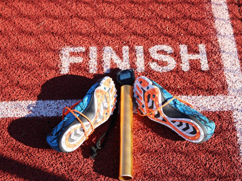 The finish line of a track with a stopwatch, baton and a pair of racing spikes on it.